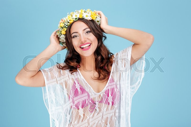 Stock image of 'Close-up portrait of a beautiful brunette wearing flower wreath isolated on the blue background'
