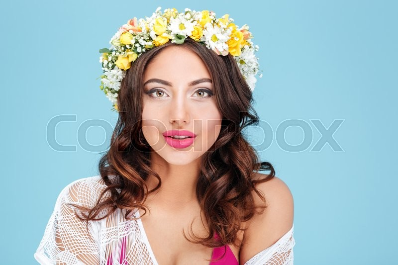 Stock image of 'Close-up portrait of a sexy brunette wearing flower diadem isolated on the blue background'