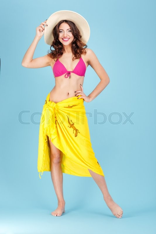 Stock image of 'Beautiful cheerful beach girl wearing swimsuit and hat isolated on the blue background'