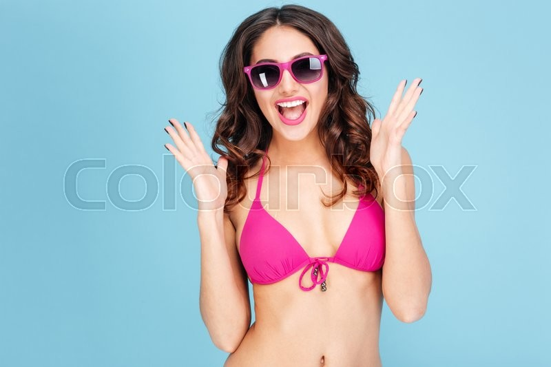Stock image of 'Portrait of a happy smiling young woman in sunglasses and bikini isolated on the blue background'