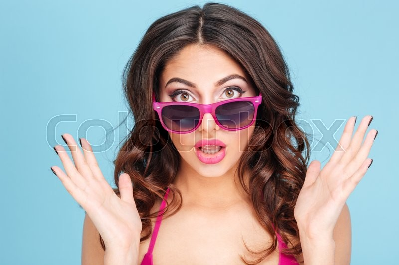 Stock image of 'Close-up portrait of a surprised pretty girl in sunglasses over blue background'