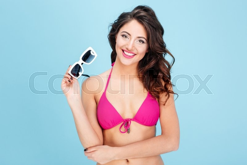 Stock image of 'Close-up portrait of an attractive young girl holding sunglasses isolated on the blue background'