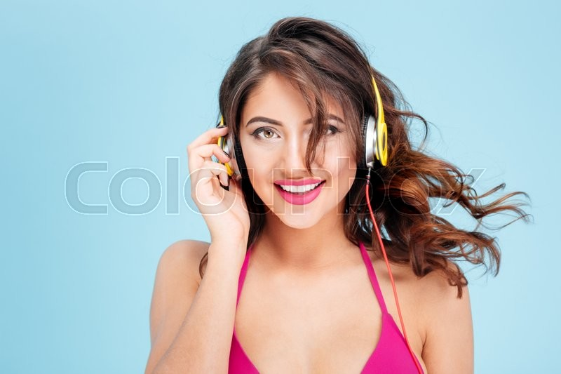 Stock image of 'Close-up portrait of smiling attractive girl listening music with earphones isolated on the blue background'