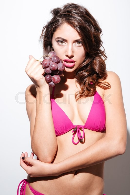 Stock image of 'Sexy beautiful brunette holding grapes isolated on the white background'