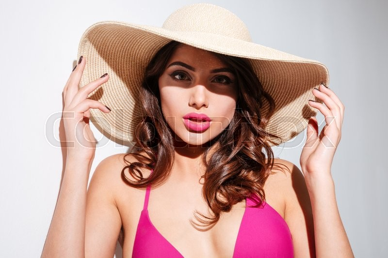 Stock image of 'Close-up portrait of an attractive sexy woman in beach hat isolated on the white background'