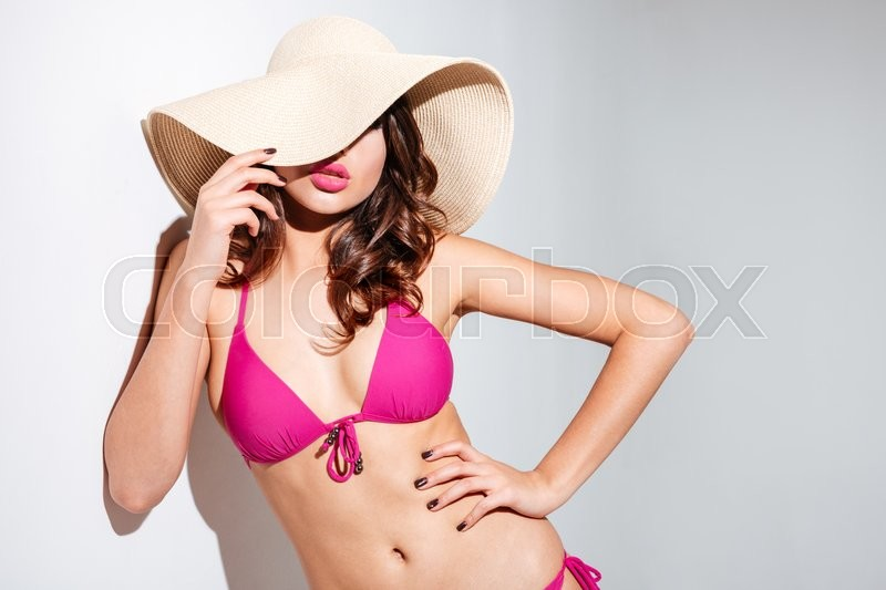 Stock image of 'Sexy beautiful brunette beach girl in hat wearing bikini isolated on the white background'