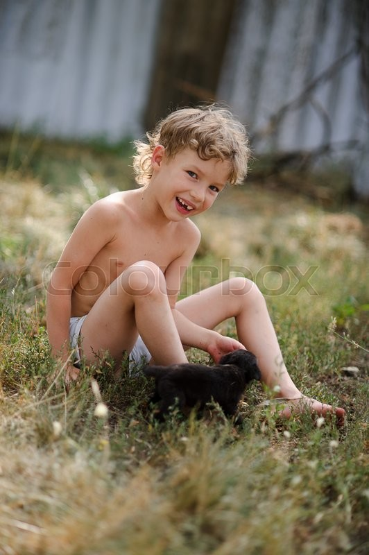 Stock image of 'The kid plays with a puppy. On the ground, covered with dry grass sits a little boy. He plays with a tiny black puppy. The boy looks into the camera and smiling.'