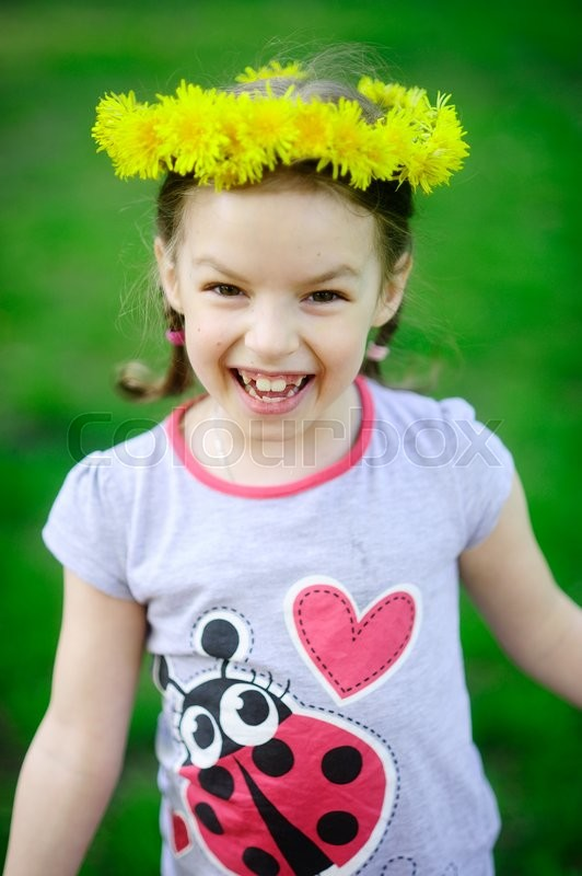 Stock image of 'The little girl in a wreath from yellow dandelions. The cheerful girl on a green background. Hair are braided in small braids. On the head a beautiful wreath. The wide smile bares large teeth.'