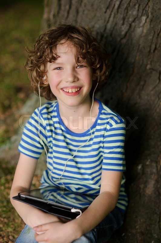 Stock image of 'The cheerful boy sits under a tree with tablet on lap. The boy has wild fair hair and blue eyes. He with a smile looks in a chamber. Behind the back trunk of a big old tree.'