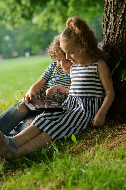 Stock image of 'Girlie and boy of 7-8 years sit under a tree having nestled and play on the tablet. Children are very keen. They with inreresy look at the screen. On their nice faces of a smile.'