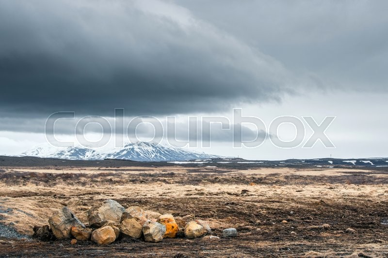 Stock image of 'Rocks on a field with mountains in cloudy weather'