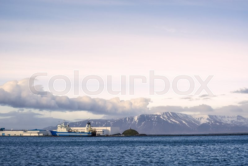 Stock image of 'Ship by the harbor in Reykjavik with a mountain in the background'
