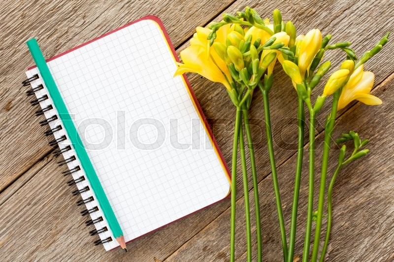 Stock image of 'Yellow freesia flowers and blank notebook on wooden background'