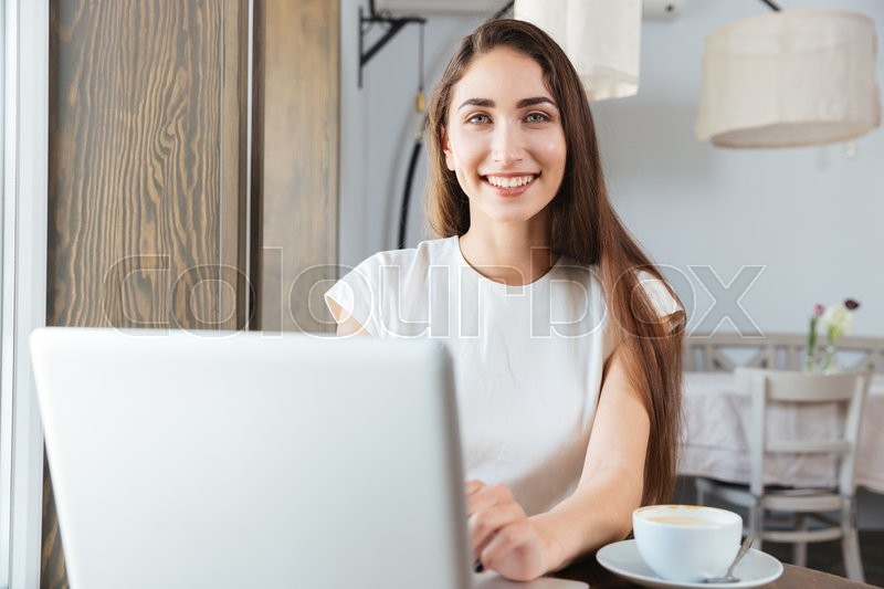 Stock image of 'Pretty young business woman using laptop for work sitting in restaurant'