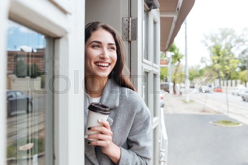 Stock image of 'Happy cheerful smiling girl holding take away coffee at the restaurant'