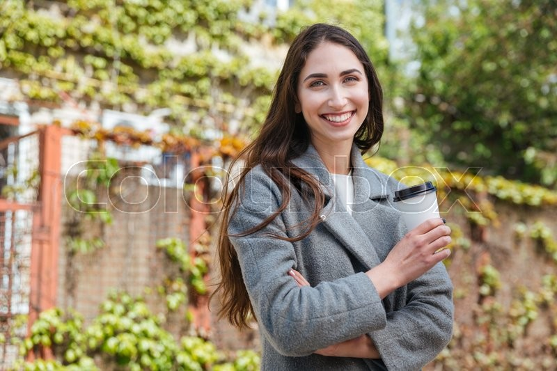 Stock image of 'Smiling beauiful cheerful girl holding take away coffe cup outdoors'