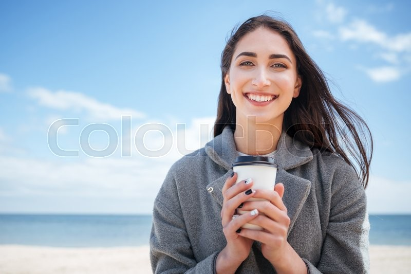 Stock image of 'Close-up portrait of a smiling cheerful girl holding takeaway cup at the seaside'