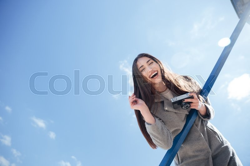 Stock image of 'Young smiling beautiful brunette woman holding camera at the seaside'