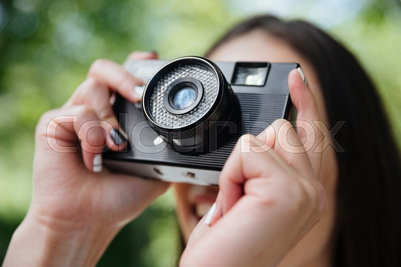 Stock image of 'Close-up portrait of a girl taking picture with photo camera outdoors'
