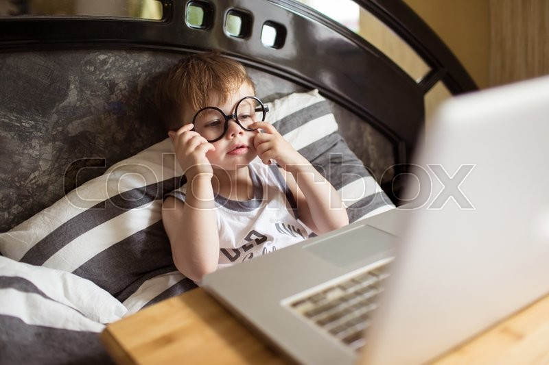 Stock image of 'Toddler boy in glasses laying on the bed and loooking to pc at home, indoors. Child with computer'