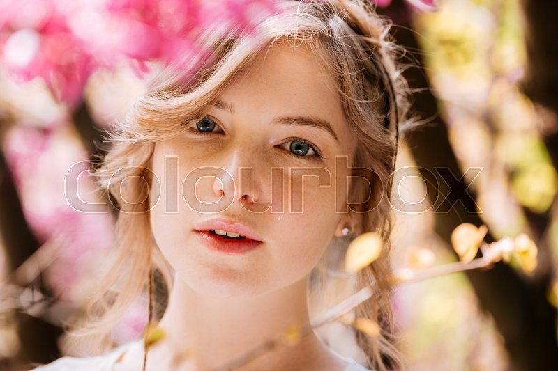 Stock image of 'Beautiful tender young woman in blooming garden'