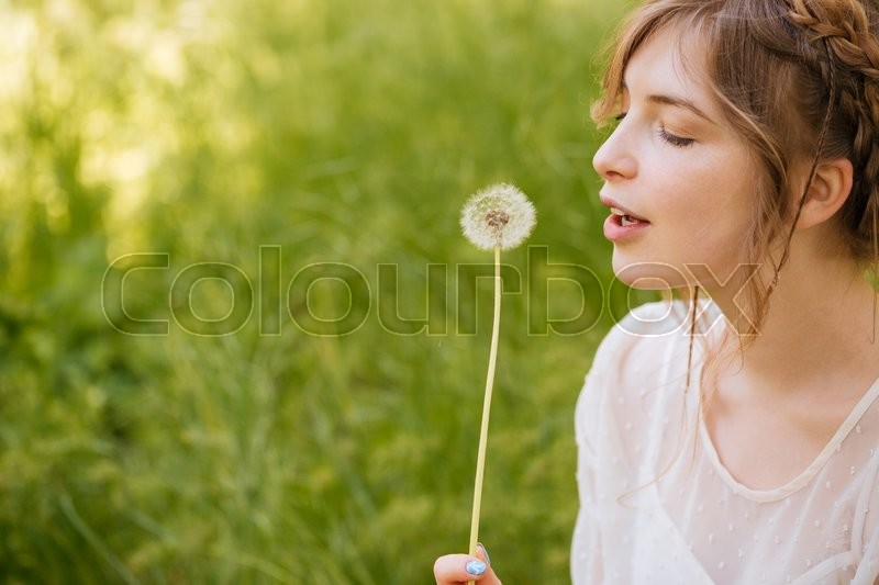 Stock image of 'Profile of cute lovely young woman holding and blowing on dandelion outdoors'