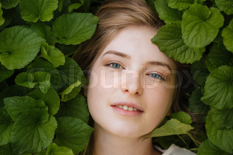 Stock image of 'Portrait of attractive tender young woman in green leaves'
