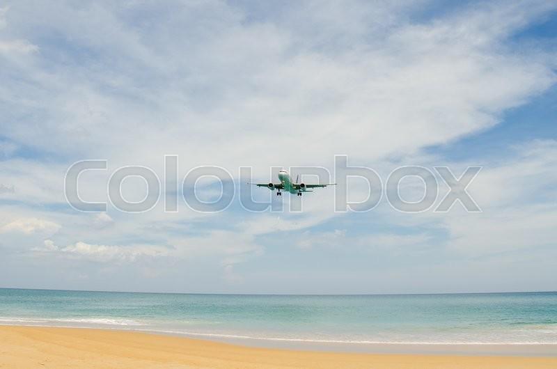 Stock image of 'Airplane landing at airport, runway near the beach.'