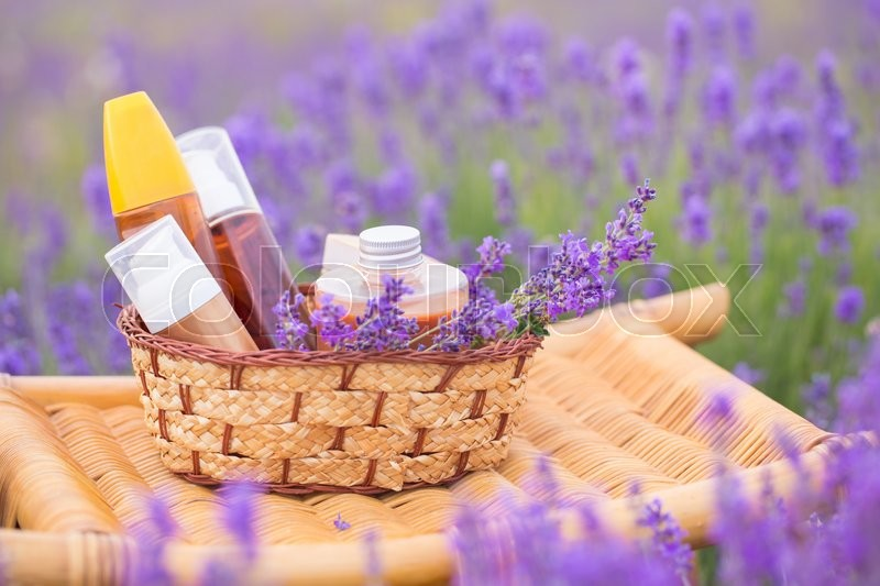 Stock image of 'Herbal soaps with flowers and group of lotions in bottles on lavender field background'