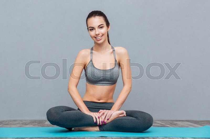 Stock image of 'Portrait of young beautiful smiling girl in grey sportswear doing yoga practice and sitting cross legged isolated on a grey background'