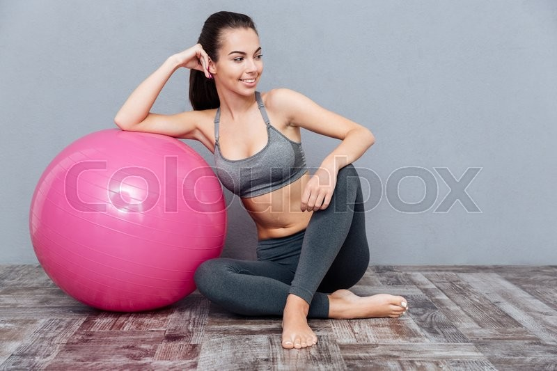 Stock image of 'Young beautiful fitness girl sitting with pink ball isolated on grey background'