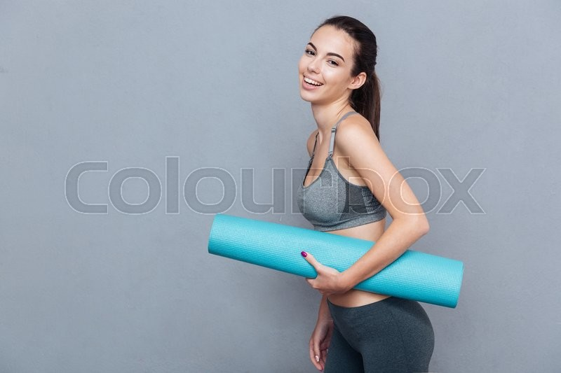Stock image of 'Attractive beautifull young sportswoman holding yoga mat isolated over grey background'