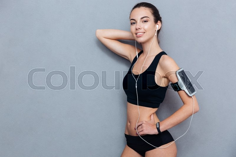 Stock image of 'Young smiling fitness girl looking at camera isolated on grey background'