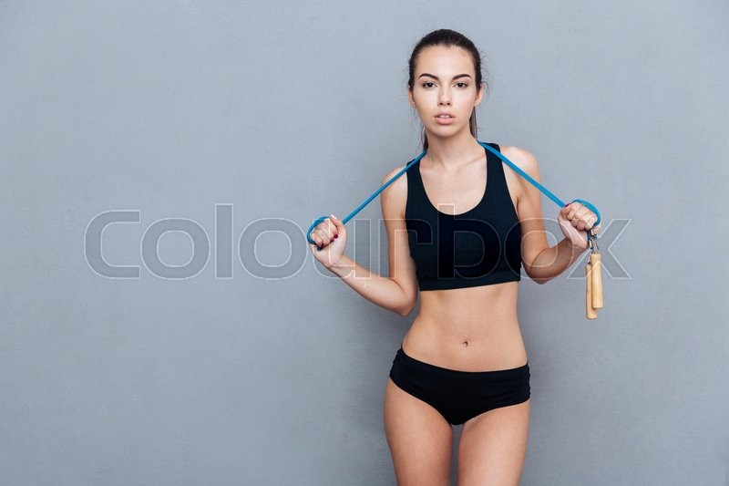 Stock image of 'Attractive sport girl holding jumping rope and looking at camera isolated on grey background'