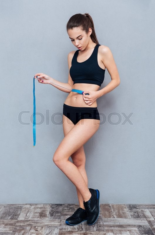 Stock image of 'Fitness woman with measuring tape isolated on grey background'