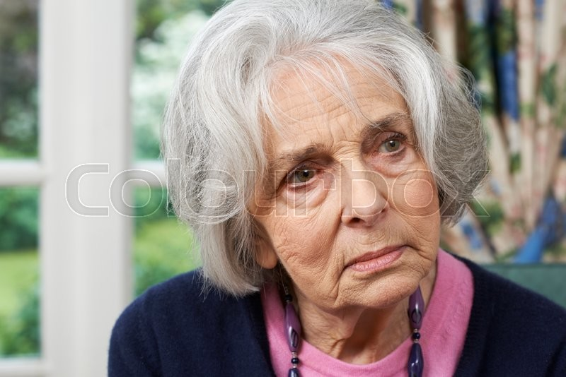 Stock image of 'Head And Shoulders Portrait Of Thoughtful Senior Woman At Home'