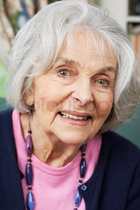 Stock image of 'Head And Shoulders Portrait Of Smiling Senior Woman At Home'