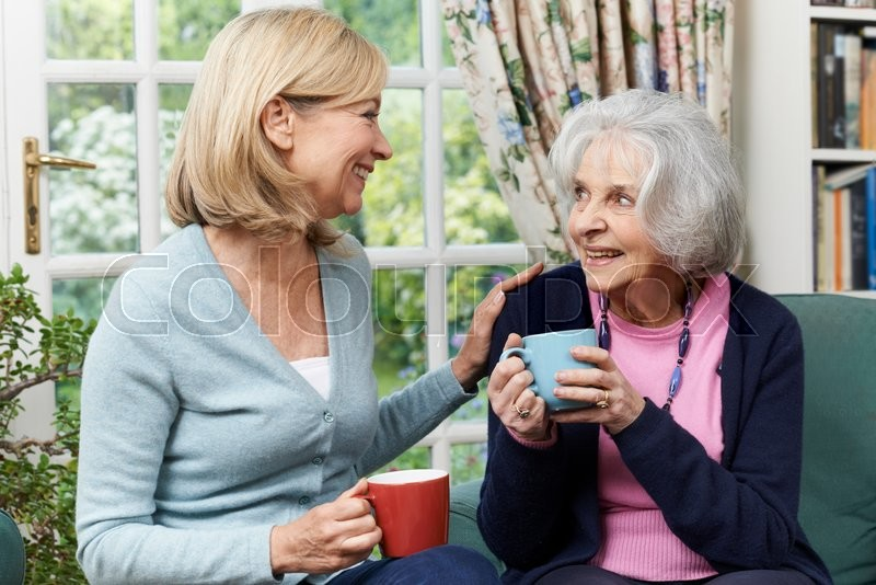 Stock image of 'Woman Taking Time To Visit Senior Female Neighbor And Talk'