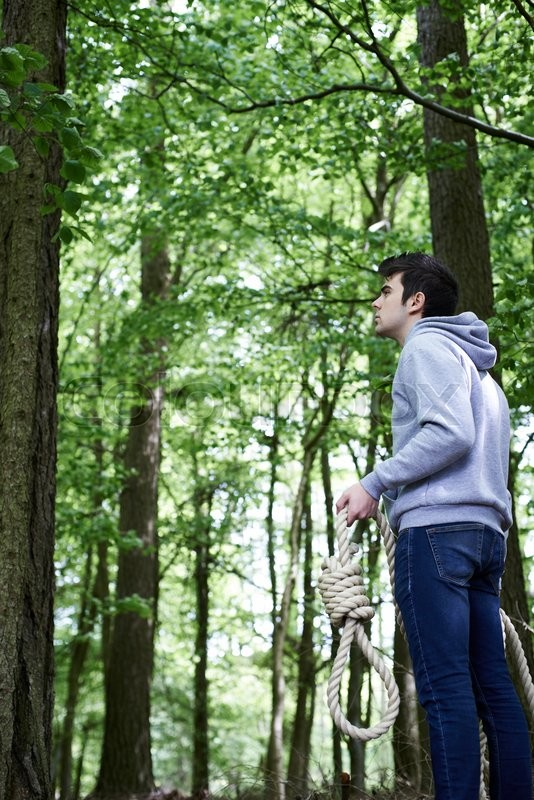 Stock image of 'Depressed Man Contemplating Suicide By Hanging In Forest'