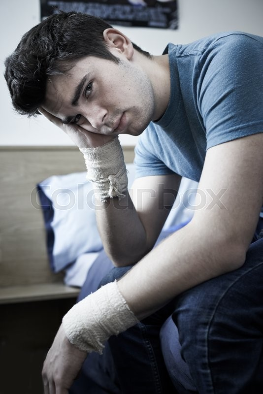 Stock image of 'Depressed Young Man With Bandaged Wrists After Suicide Attempt'