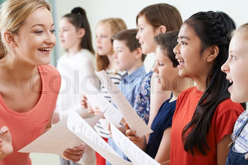 Stock image of 'Group Of Children With Teacher Enjoying Singing Group'