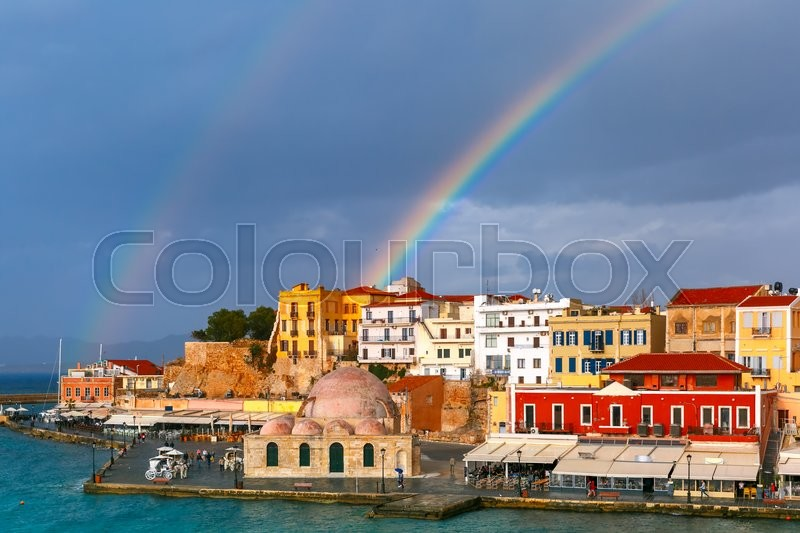 Stock image of 'Double rainbow in a cloudy sky above old harbour of Chania with Venetian quay and Kucuk Hasan Pasha Mosque in summer day, Crete, Greece'