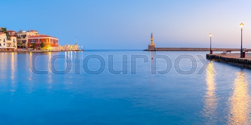 Stock image of 'Picturesque panoramic view of old harbour with Lighthouse of Chania during twilight blue hour, Crete, Greece'