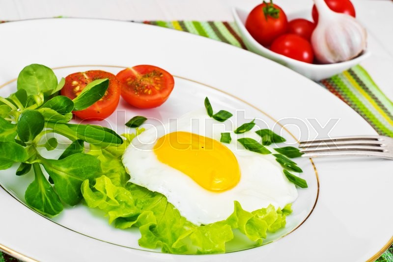 Stock image of 'Scrambled Eggs with Arugula and Tomato Health Food'