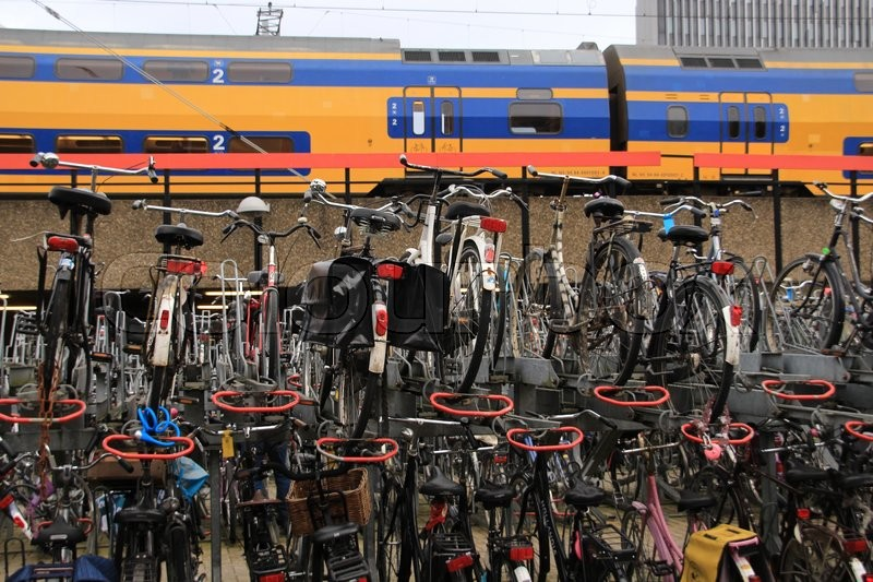 Stock image of 'Many bikes at the biking place and a coming train at the railway station in the city Leiden in spring.'