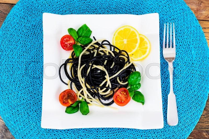 Stock image of 'Black Spaghetti with Cuttlefish Ink, Tomato and Basil. Mediterranean and Asian Cuisine. Studio Photo'