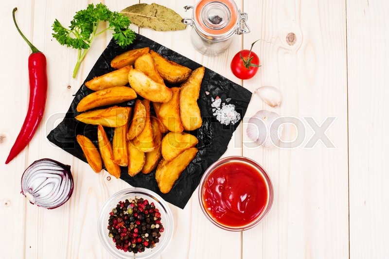 Stock image of 'Potato Wedges, Potatoes in a Rural with Tomato Ketchup Studio Photo'