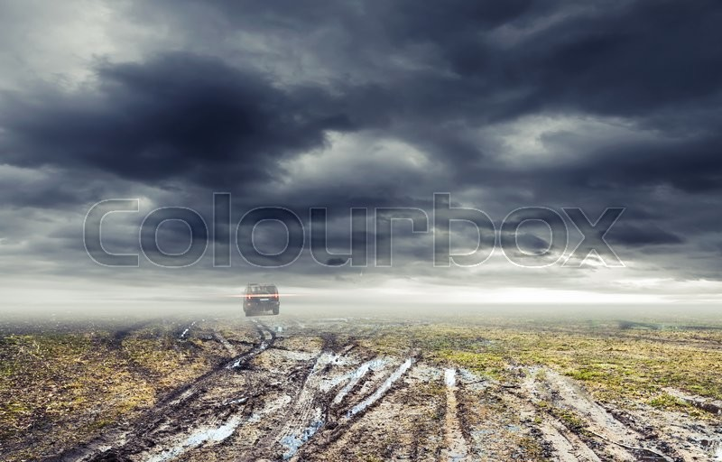 Stock image of 'Dirty rural road with puddles and mud under dark dramatic stormy sky, SUV car goes far away, transportation background'