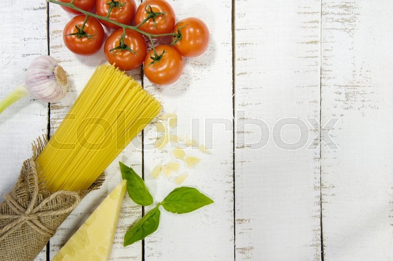 Stock image of 'Food frame. Pasta ingredients. Cherry-tomatoes, spaghetti pasta, garlic, basil, parmesan and spices on  white  background, copy space, top view, horizontal oriented'