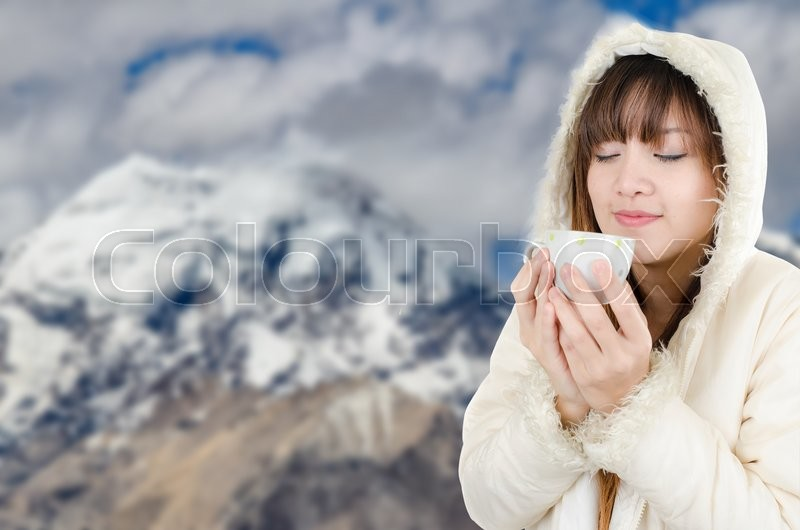 Stock image of 'Beautiful Woman with winter anorak and mug of hot tea with blurry background of snow mountain'